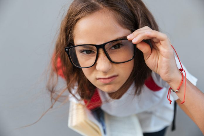 Perdas na economia devido à pandemia durarão até o fim do século, diz OCDE; imagem mostra menina com mão no óculos e livro no braço olhando em direção à câmera