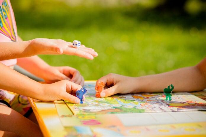 Jogos de tabuleiro para alugar – uma boa opção para divertir toda a família; imagem mostra mãos de crianças sobre tabuleiro mexendo em peças azul e vermelha