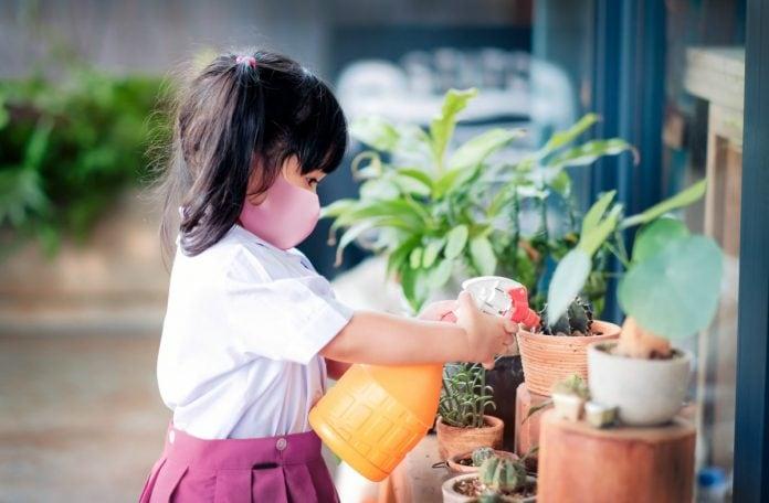 É preciso reabrir as escolas e aprender como elas funcionam, diz diretor de Fundação Lemann; imagem mostra garotinha de máscara regando plantas