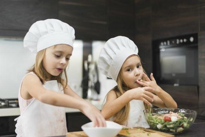 3 receitas que as crianças adoram (e usam alimentos da época); na imagem, duas meninas com chapéu de cozinheiro e avental preparam salada