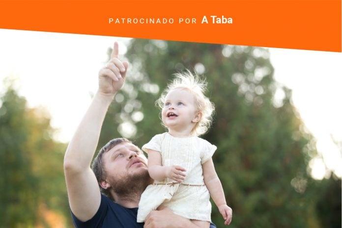 A importância da comunicação entre pais e o bebê; imagem mostra pai segurando bebê no ombro esquerdo e apontando para o céu em espaço ao ar livre com verde ao fundo
