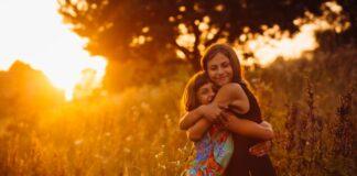 O abraço: 'Escolha quem você quer abraçar, porque abraço faz falta'; imagem mostra mãe e filha se abraçando em meio ao campo com o por do sol ao fundo