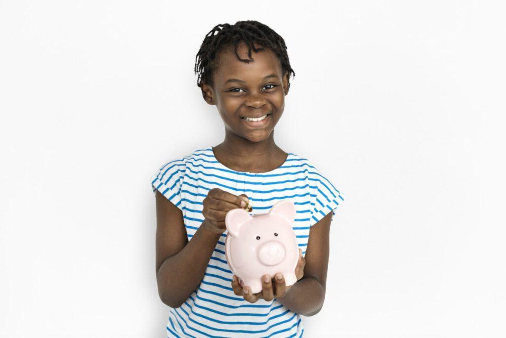 Semanada ou mesada: qual é o mais indicado para o seu filho?; imagem mostra garota de camiseta listrada azul sorridente segurando cofrinho de porquinho cor-de-rosa
