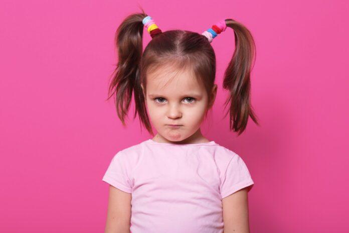 Toda criança adora fazer birra, mas será que é birra mesmo?; imagem mostra menina com o cabelo preso dos dois lados de camiseta rosa clara num cenário rosa choc