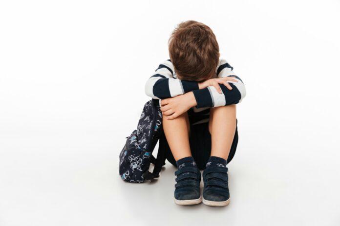 Por que a punição e o castigo não devem ser usados com as crianças;, imagem mostra menino sentado no chão com joelhos dobrados e rosto escondido sobre eles