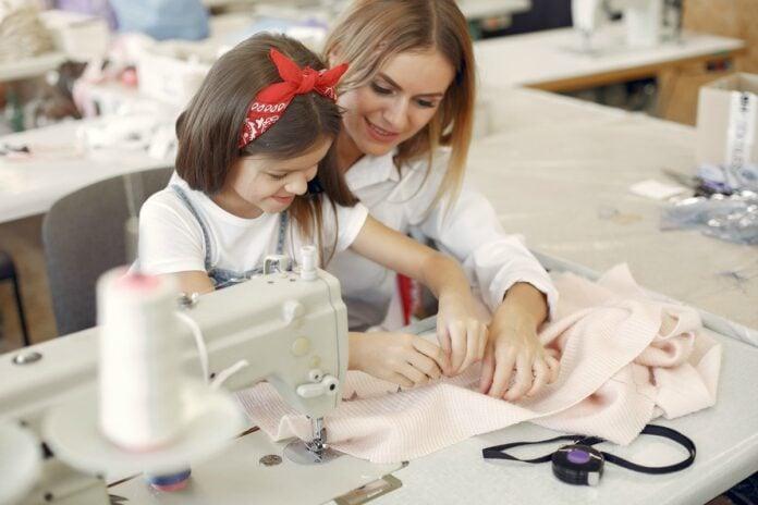O objetivo da educação empreendedora é aproveitar um potencial presente em todos nós, mas pouco estimulado pela escola e pela família; imagem mostra mulher adulta e menina mexendo em máquina de costura
