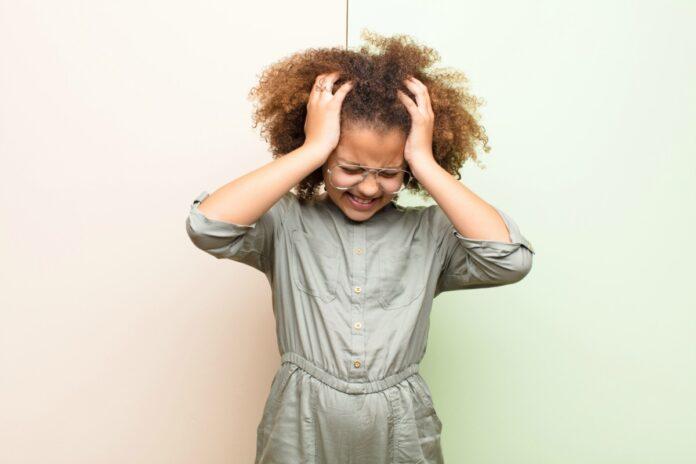 Dor de cabeça nas crianças: saiba as 4 causas mais comuns; imagem mostra garota de cabelos crespos com as mãos na cabeça e expressão de dor