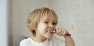 Dicas para estimular a escovação correta dos dentes nas crianças; imagem mostra menino de cabelos claros escovando os dentes em frente ao espelho