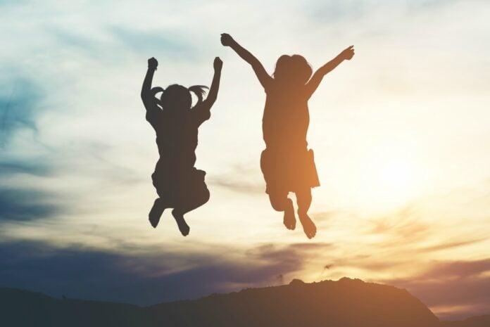 'O Começo da Vida 2: Lá Fora' – filme destaca importância de reconectar com a natureza; imagem mostra duas crianças suspensas no ar com o pôr do sol ao fundo