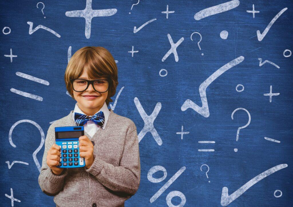3 a cada 4 pais dizem já saber a carreira que os filhos irão seguir; imagem mostra garoto de óculos, terno e gravata borboleta azul segurando uma calculadora, ao fundo uma lousa azul tem símbolos matemáticos escritos
