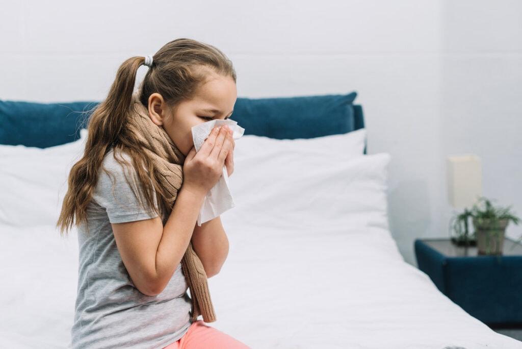 Rinite e conjuntivite alérgicas nas crianças: veja os cuidados a tomar; imagem mostra menina assoando o nariz com papel branco