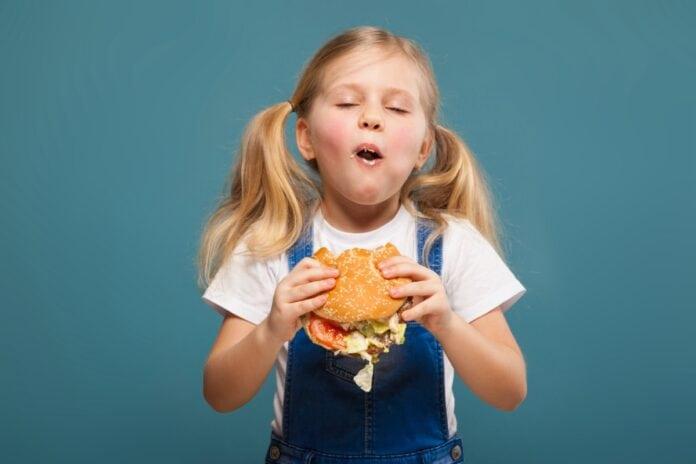 O que comemos e que comidas damos aos nossos filhos: presença de agrotóxicos em alimentos e riscos dos ultraprocessados despertam alerta; menina come hamburguer