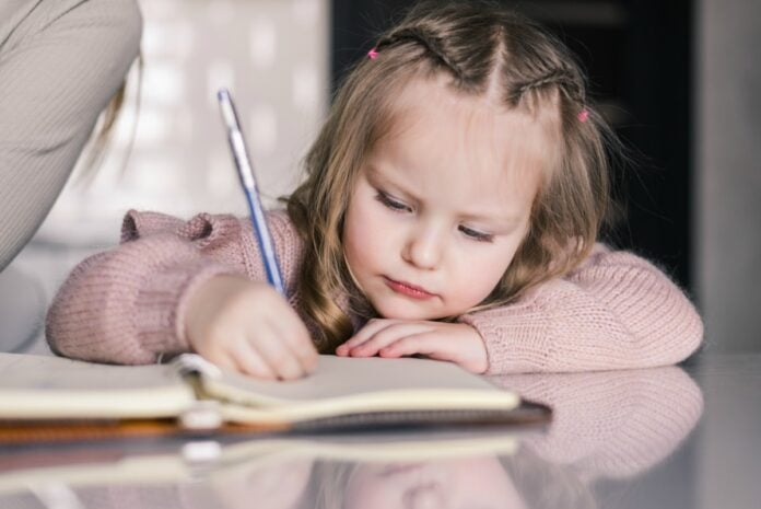 Seu filho sabe segurar o lápis corretamente? Veja como ajudá-lo; imagem mostra menina de 4 ou 5 anos escrevendo em um caderno