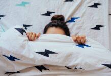 Preguiça: um vilão necessário; imagem mostra rosto de mulher na cama coberto por edredon até metade da testa