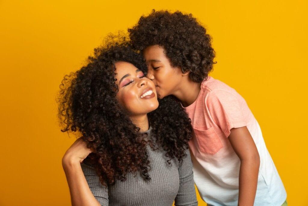 7 dicas para promover uma educação livre do machismo; imagem mostra criança morena dando beijo na mãe morena