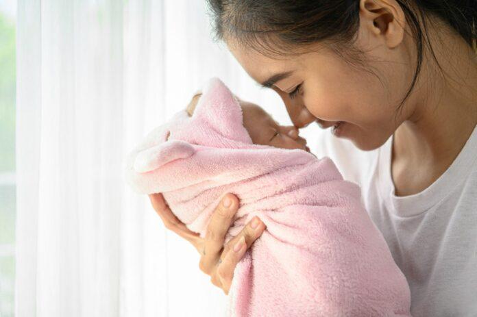 Em busca de um parto normal, grávidas largam plano e optam pelo SUS; imagem mostra mãe segurando bebê recém-nascido enrolado em manta rosa