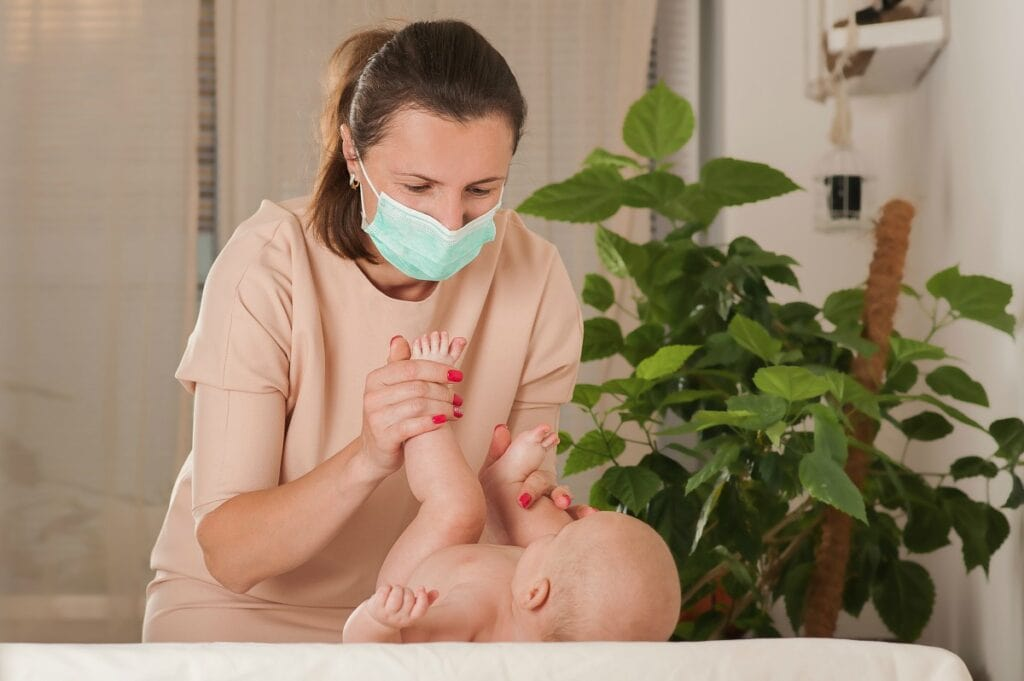 Ministério da Saúde alerta sobre uso de máscara em recém-nascidos e criança de até 2 anos; imagem mostra mãe usando máscara e segurando perna de bebê deitado