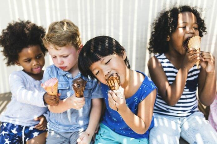 Como falar sobre racismo com as criancas: 5 atitudes a seguir; imagem mostra quatro crianças sentadas tomando sorvete, sendo duas delas negras, um loiro e outro oriental