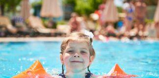 SBP alerta para risco de afogamento das crianças ao ficarem sozinhas em piscinas, sem supervisão de um adulto; imagem mostra menina em piscina com boias nos braços