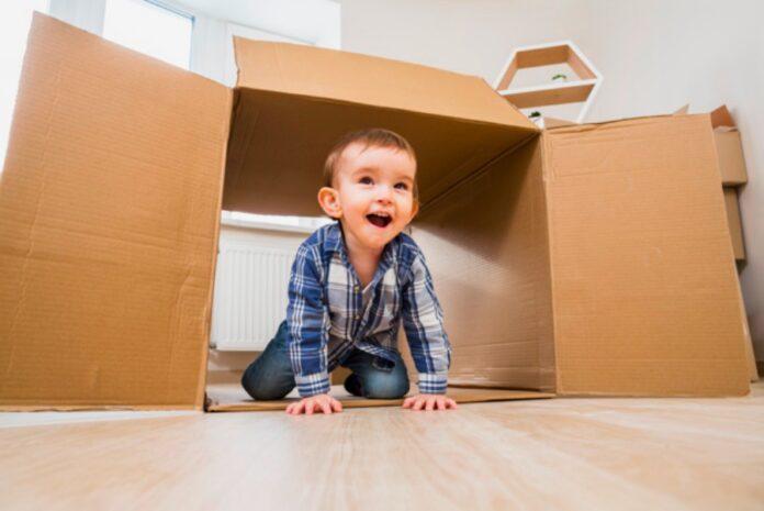 12 brincadeiras para divertir e ensinar crianças de todas as idades!; menino sorridente anda dentro de caixa de papelão