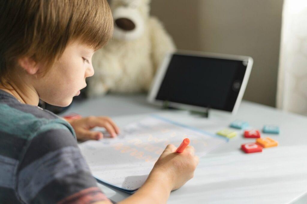 Aplicativos de alfabetização que ensinam e divertem as crianças; garoto escreve em folha de carderno com notebook ao fundo