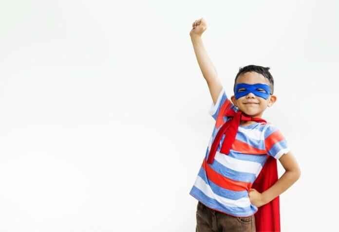 Como incentivar nossos filhos para que sejam corajosos e prudentes?; garoto de máscara azul nos olhos e capa vermelha está com o braço levantado