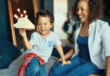 Fazer menos e melhor – mais simples, prático, e bonito; mãe olha sorridente para filho que segura aviãozinho de origami na mão