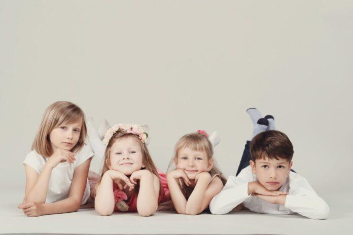 Existem diferenças entre os filhos?; quatro crianças estão deitadas no chão com o queixo apoiado nas duas mãos