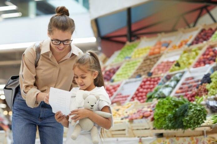 4 dicas para agir de forma pro ativa e evitar o mau comportamento infantil; mãe confere lista de compras com filha junto a seção de verduras do supermercado