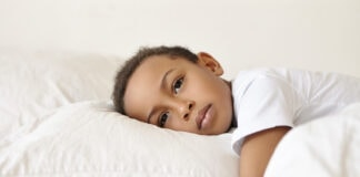 4 maneiras como o racismo afeta o cérebro da criança, segundo Harvard; Menino negro triste deitado em cima de travesseiro