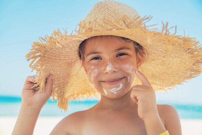 Câncer de pele: cuidados com exposição solar começam na infância; garoto passa protetor no rosto e usa chapéu de palha