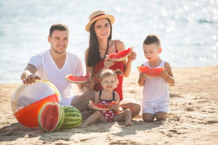 Veja opções de lanches caseiros rápidos para as crianças neste verão; família sentada na areia da praia comendo melancia