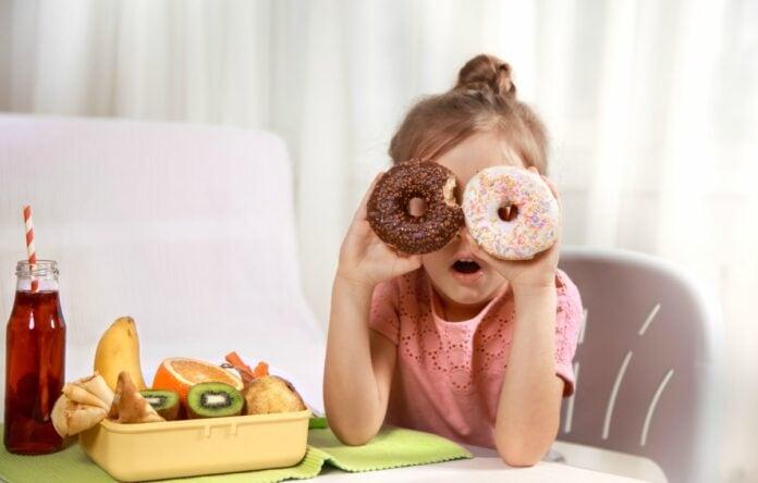 Pediatra dá dicas de como reduzir consumo de guloseimas pelas crianças; garota apoia cotovelos sobre mesa e segura um 'donut' em cada olho, na mesa há frutas e uma bebida