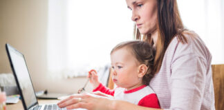 Home office na pandemia afeta mais famílias com crianças pequenas; mãe de olhos fechados e cabeça abaixada segura bebê junto ao peito