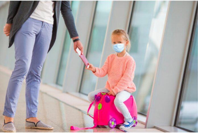 Brasil exige teste de covid-19 de para entrar no Brasil, exceto de crianças; garota sentada em cima da mala com mão dada com a mãe em aeroporto