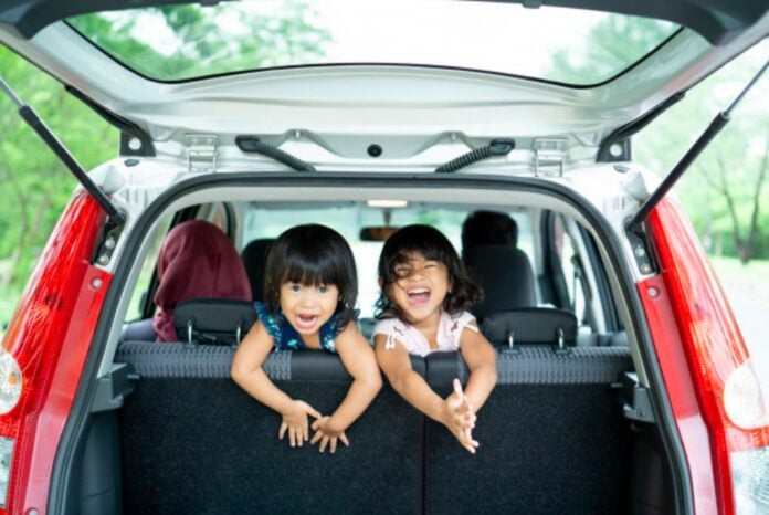 Viagem de carro em família: dicas para um passeio tranquilo (e divertido!); duas meninas estão de joelhos no banco traseiro de um carro olhando para trás com o porta malas aberto