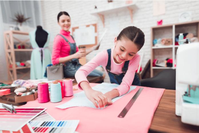Empreendedorismo é uma forma de ser – e isso tem a ver com família; menina corta tecido junto à máquina de costura e mãe olha ao fundo