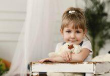 Crianças precisam saber que são antifrágeis e evoluem com os desafios; garota está abraçada a urso de pelúcia branco e olha fixamente para a câmera