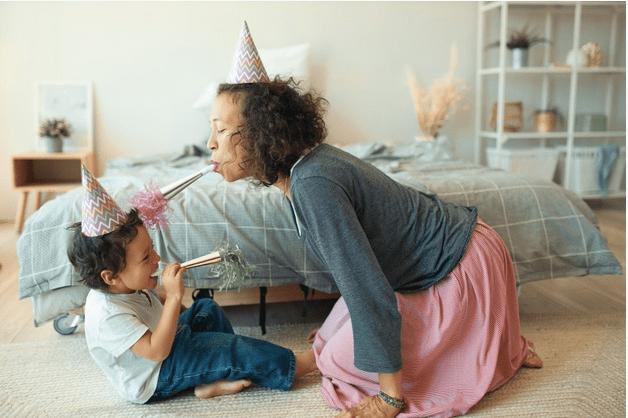 Desejo para 2021: saúde e compromisso com a infância; mãe e filho brincam no chão ao lado da cama, ambos com chapéu de cone na cabeça