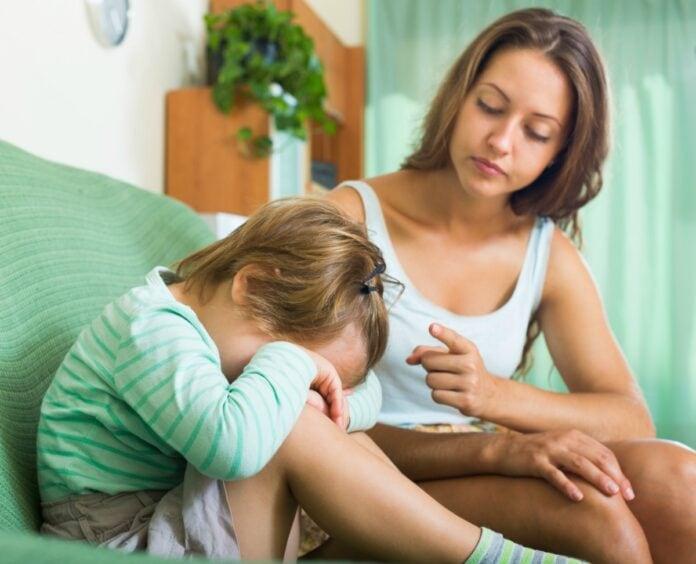 3 atitudes tóxicas que contaminam o ambiente familiar; mãe olha para filho que está de cabeça baixa no sofá