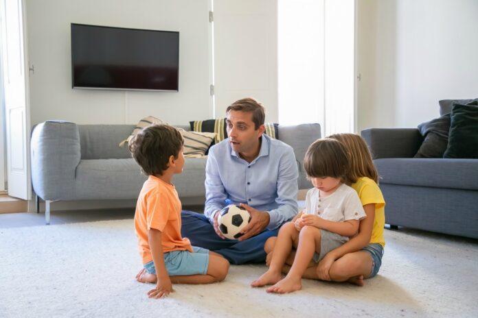 7 passos para promover a comunicação não violenta com as crianças; pai segura bola no colo e conversa com 3 crianças, todos sentados no chão