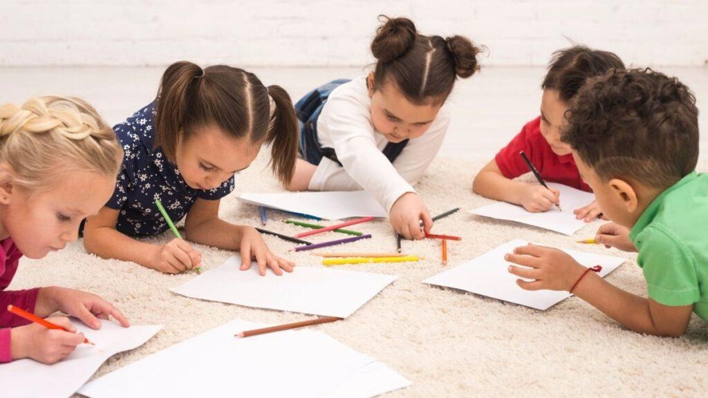 Cinco crianças deitadas no chão desenhando sobre folhas de papel com lápis de cor