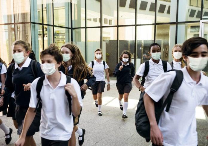 Como as escolas particulares se preparam para o retorno do ano letivo; alunos caminham de máscara em espaço escolar