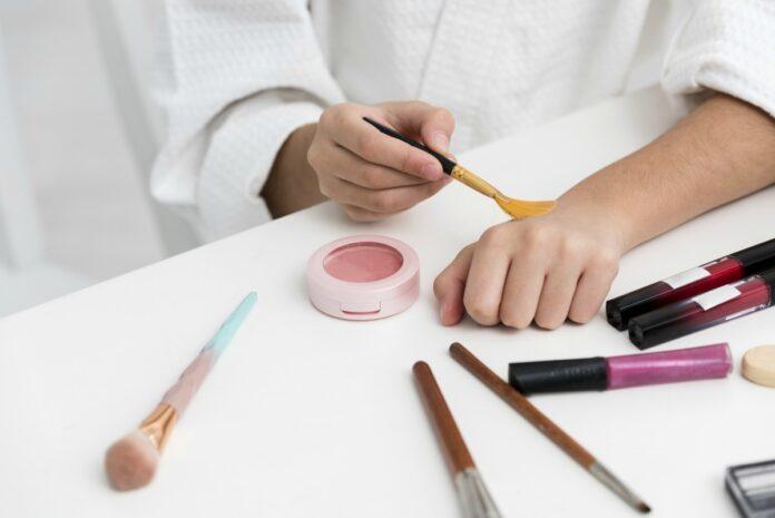 Maquiagem infantil: veja os cuidados a tomar ao escolher os produtos; mão de criança passa maquiagem no punho com pincel