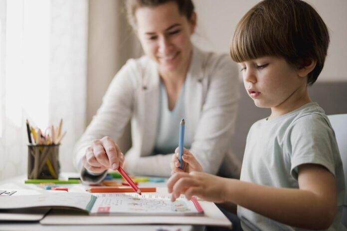 10 dicas de como organizar o cantinho de estudos das crianças; mãe observa filho desenhando em papel sobre mesa