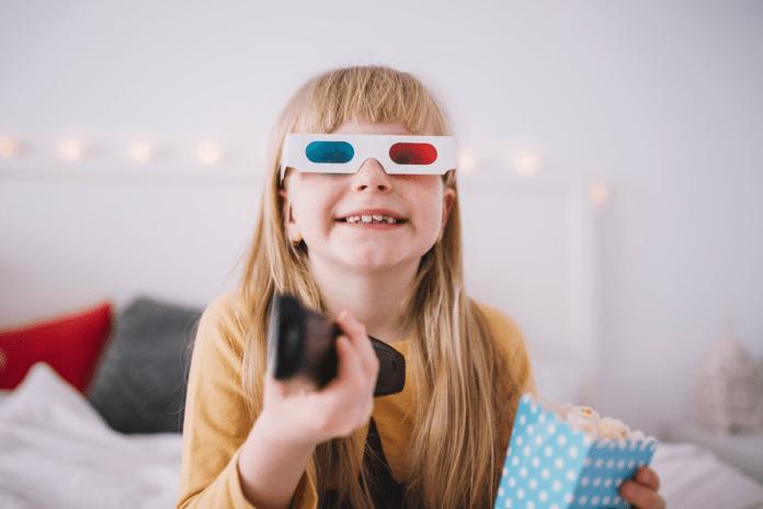 Quanto maior o tempo de TV da criança, maior o estresse dos pais; menina loira com óculos 3D sorri e segura controle remoto com a mão
