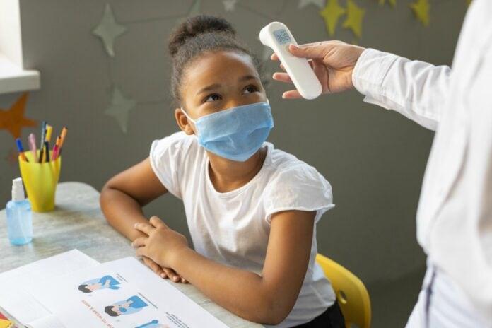 Pelo menos 15 estados pretendem retomar aulas presenciais em 2021; aluna de máscara mede temperatura em sala de aula