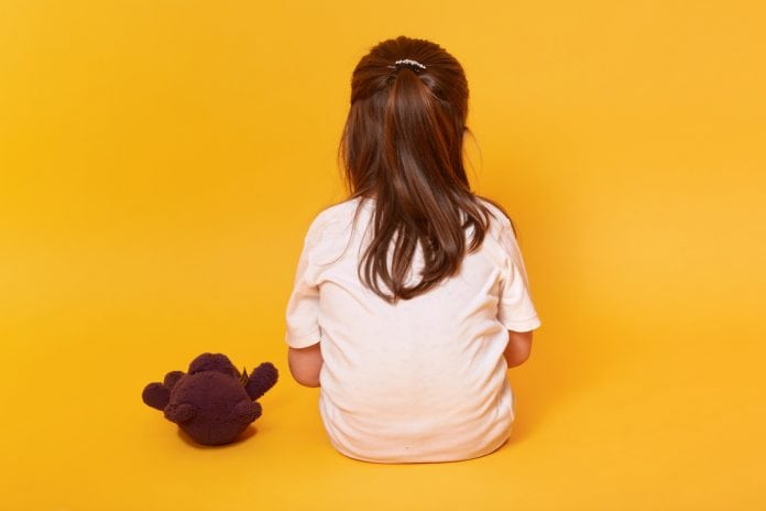Projeto busca conscientizar crianças sobre abuso sexual; criança de cabelo liso grande está sentada no chão de costa com urso de pelúcia ao lado em imagem de fundo amarelo