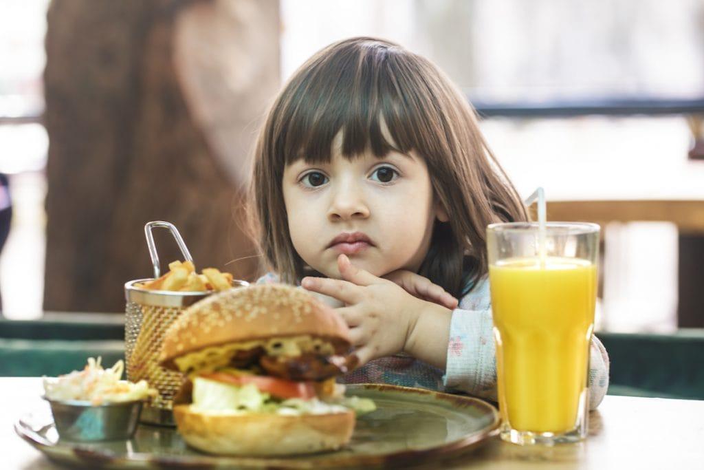 Gordura e açúcar na infância podem alterar o microbioma por toda a vida; criança pequena segura batata frita que está sob mesa junto a hambúrguer e suco