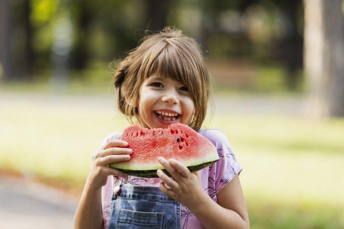 9 alimentos que ajudam na hidratação das crianças; menina sorridente de macacão jeans e blusa rosa segura melancia com as duas mãos